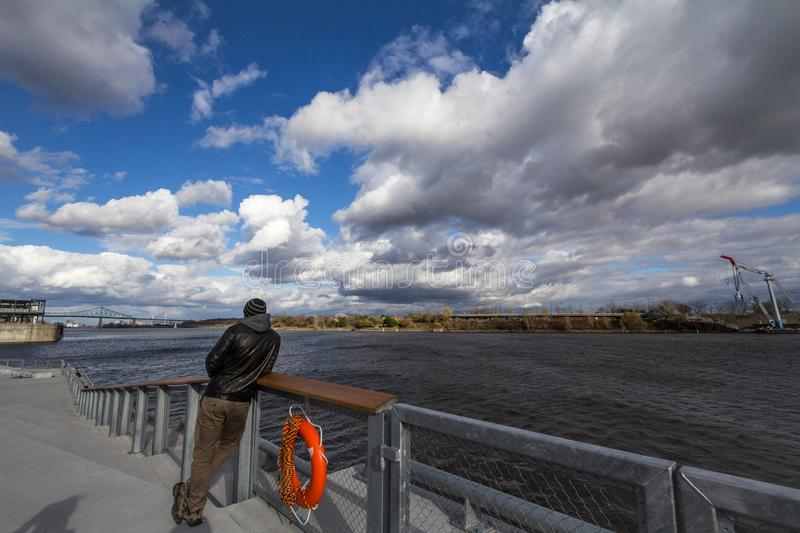 Man standing watching Saint Lawrence river in Montreal, Quebec. royalty free stock images