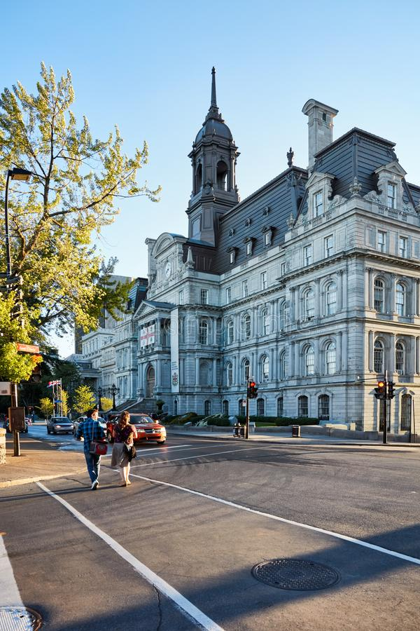 Montreal city hall L`hotel de ville and a Canadian couple crossing the street on a sunny summer afternoon in Montreal, Quebec, stock photo