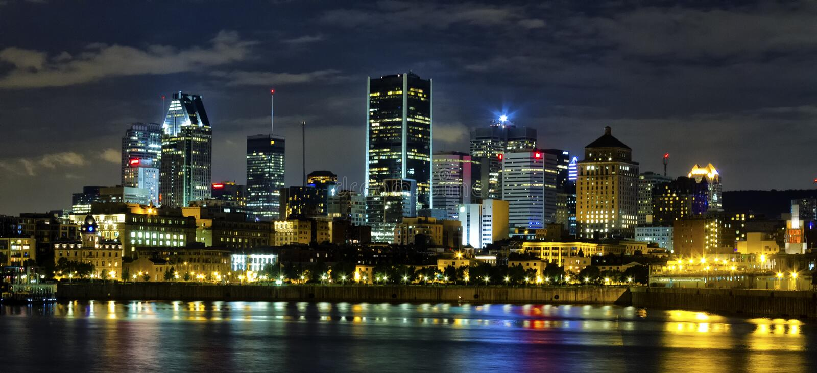 Montreal by night. Part of the Montreal skyline at night with the old port in the foreground stock photo