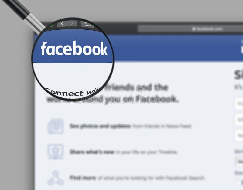 Montreal, Quebec, Canadá - 7 de agosto de 2019: Homepage de Facebook con el logotipo en una lupa fotos de archivo