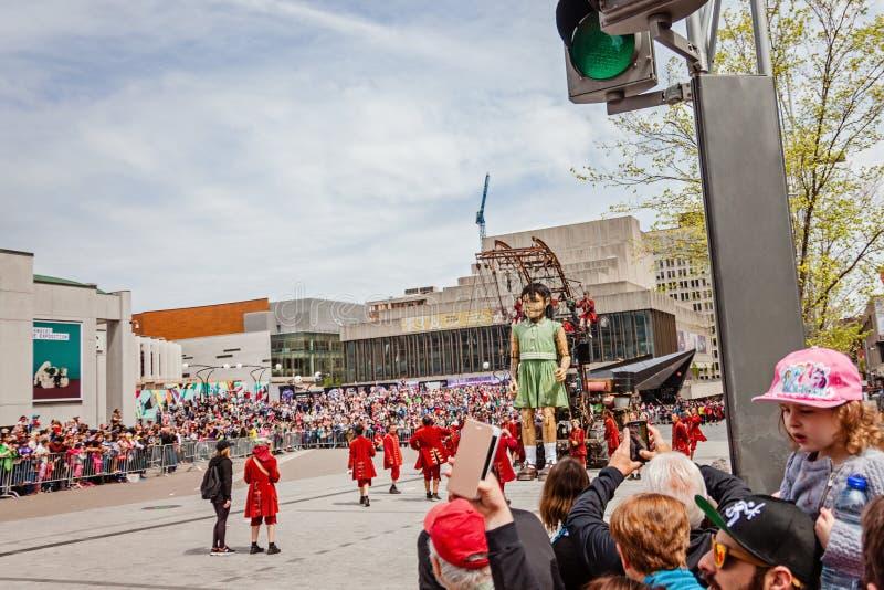 Montreal, Quebeque, Canadá - 21 de maio de 2017: A multidão que olha o marionete de passeio gigante da menina fotos de stock royalty free
