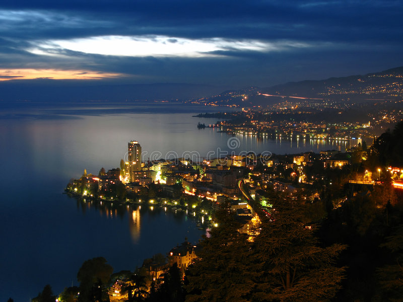 Montreux at night, Switzerland. View of the Swiss Riviera from the heights of Montreux (Glion) spreading along the rough coast of Lake Geneva which reflects the stock photo