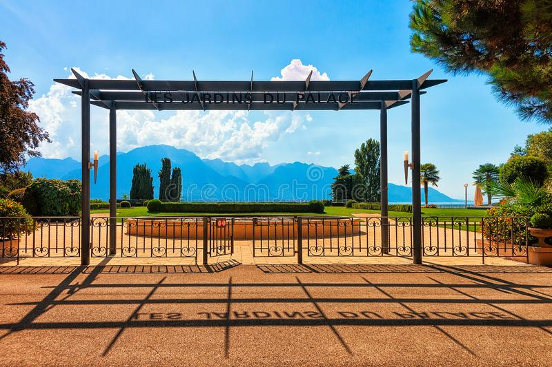 Montreux, Switzerland - August 28, 2016: Entrance into garden at Geneva Lake in Montreux, Swiss Riviera. Alps mountains on the. Background stock photography