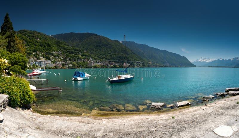 Montreux VD/Schweiz - 31 Maj 2019: fartyg på kusterna av sjöGenève med stor sikt av de schweiziska fjällängarna bakom som sett fr royaltyfria foton