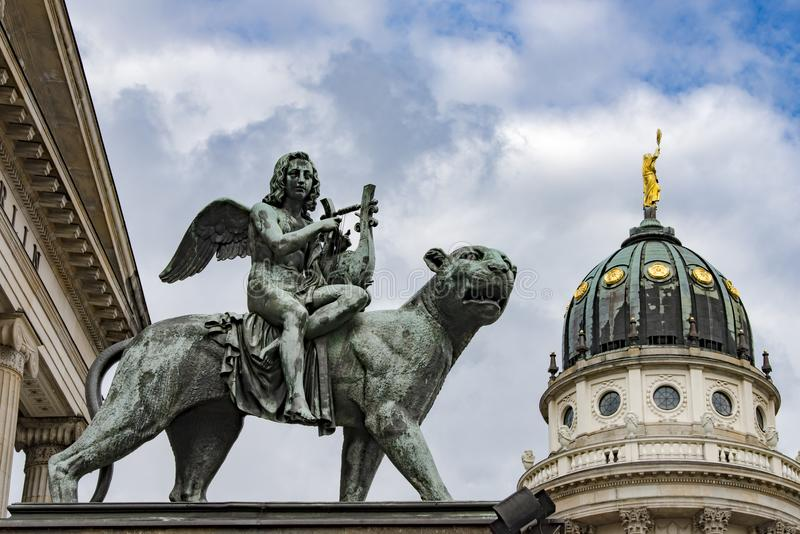 Monument of angel playing harp on Gendarmenmarkt, Berlin. Angel on lioness at music hall Konzerthaus in front of Dome French Cathedral on Gendarmenmarkt in stock images