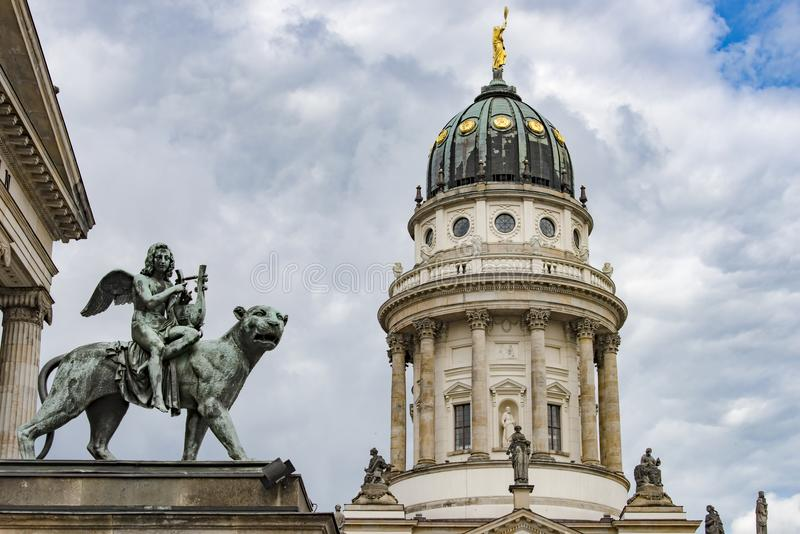 Monument of bronze angel playing harp on Gendarmenmarkt, Berlin. Angel sitting on lioness at music hall Konzerthaus in front of Dome French Cathedral on royalty free stock images