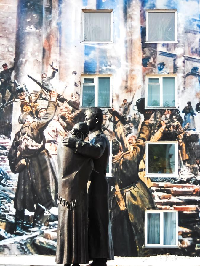 Monument dedicated to the war on the background of a poster depicting soldiers stock photos