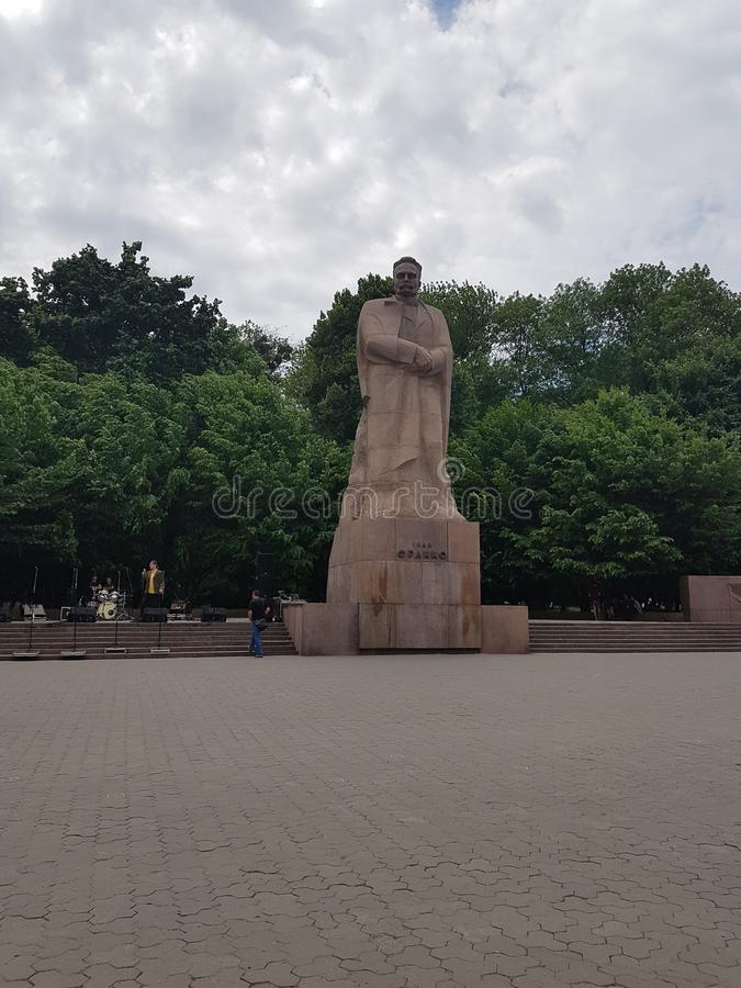 Monument of Ivan Frank from the brown stone, in the square under the open sky, which is covered with dark clouds. Behind the monu stock image