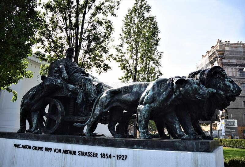 Monument with man in clothes, perhaps of ancient Roman, seated on a small seat with wheels, pulled by lions in Vienna. stock images