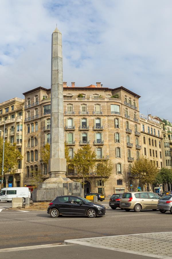 Monument in the shape of an obelisk of gray granite, Plaza Cinc d`Oros, Barcelona, Spain. stock image
