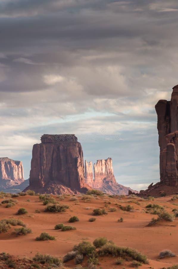 Monument-Tal bei Sonnenaufgang mit Sandsteindünen im Vordergrund lizenzfreie stockfotos