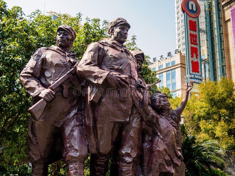 Monument till folkets befrielsearméPLOMMONERNA på den Nanjing vägen, Shanghai, med den nya världsEmporiumgallerian i bakgrunden - arkivfoton