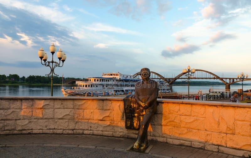 Monument till Lev Oshanin på strand av Rybinsk på solnedgången royaltyfria bilder
