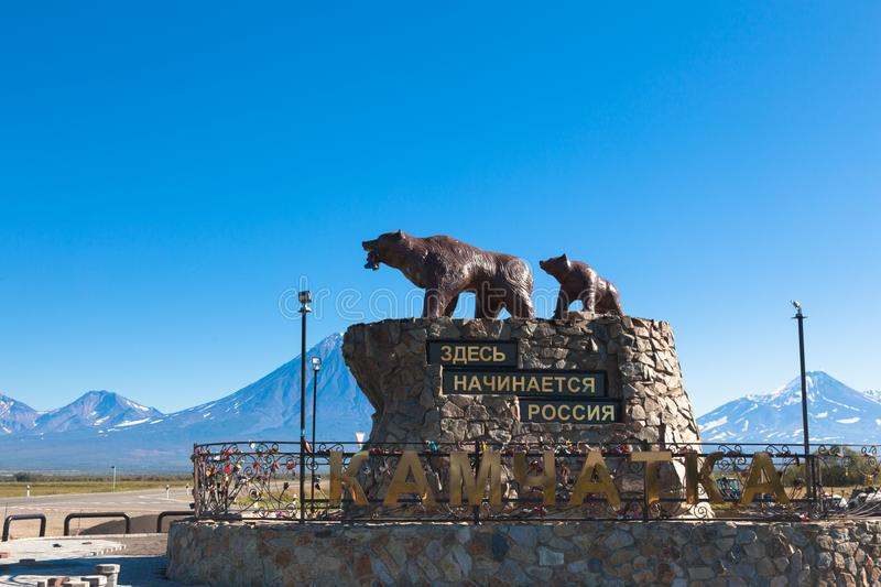 Monument to the bears in Kamchatka in the city of Petropalovsk Kamchatka on the background of volcanoes and blue sky. The inscription translates as `Russia royalty free stock images