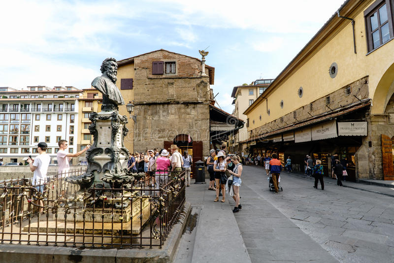 Monument to Benvenutto Cellini on one side of the bridge over the river Arno, called `Ponte Vecchio` with people walking stock photography
