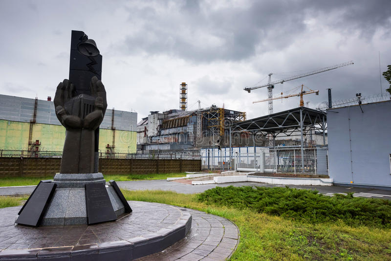 Monument to the Chernobyl liquidators with fourth reactor on the background. Monument to the Chernobyl catastrophe liquidators with fourth reactor on the royalty free stock photo