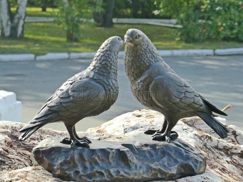 Monument to lovers student couples. The sculpture consists of two huge cooing pigeons and a bronze plate `hands of love`. Yekaterinburg, Russia royalty free stock photo