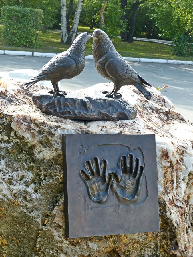 Monument to lovers student couples. The sculpture consists of two huge cooing pigeons and a bronze plate `hands of love`. Yekaterinburg, Russia royalty free stock image