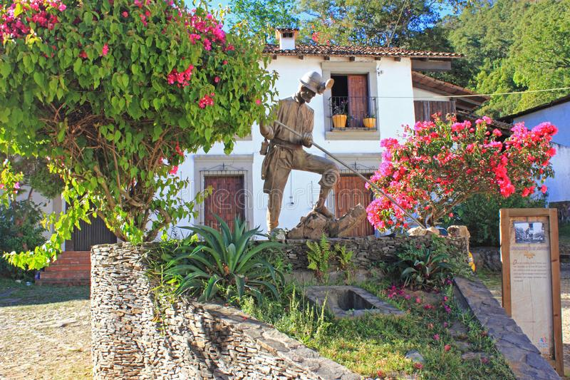 Miner`s Statue, San Sebastian, Mexico. Monument to miners with bougainvilleas and oldstyle house in background. Soft morning sunlight. Historic mining town of stock photography