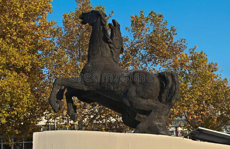 Monument of two horses in front of autumn trees.  royalty free stock photography