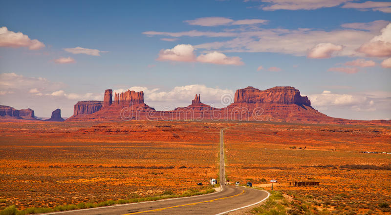 Monument Valley. Road leading to distant Monument Valley rock formations stock photos