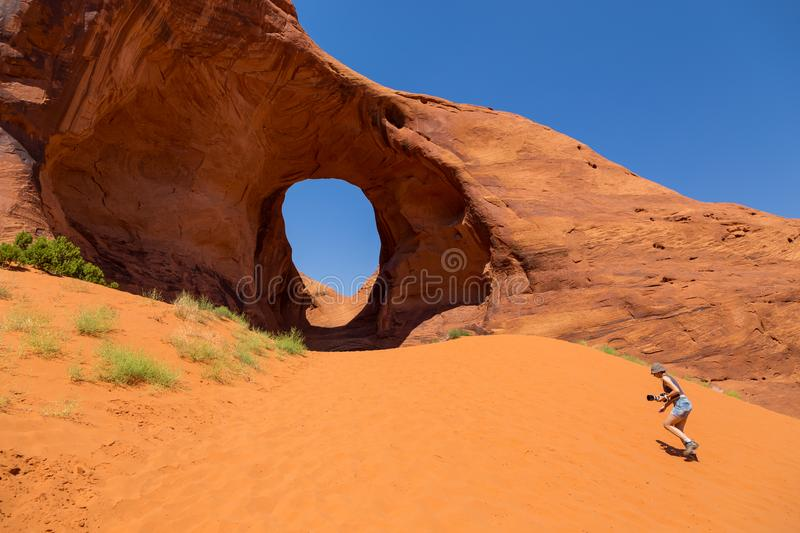 Girl at Ear of the Wind. Pothole natural arch eroded in sandstone. stock photos