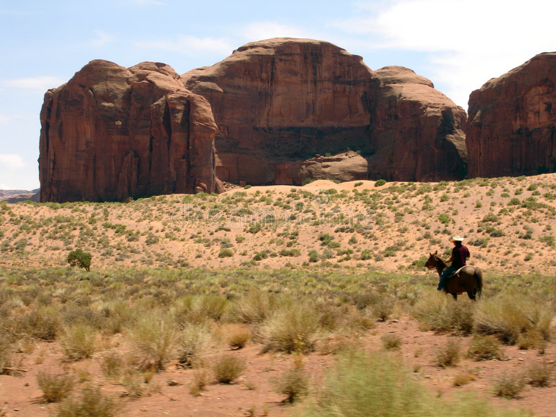 Monument Valley cowboy. Riding cowboy with horse in Monument Valley with rocks in the background - UTAH USA royalty free stock photography