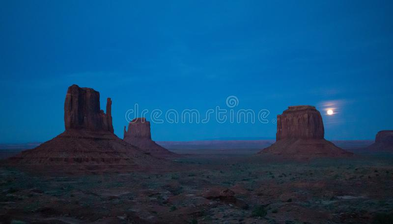 Monument Valley Tribal Park in the Arizona-Utah border, USA. Monument Valley, Fullmoon in spring. Red rocks against dark blue sky. Navajo Tribal Park in the stock photos