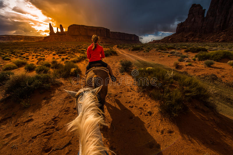 Monument Valley Horseback Riding. First person view from the horse with sunset sky over the three sisters royalty free stock image