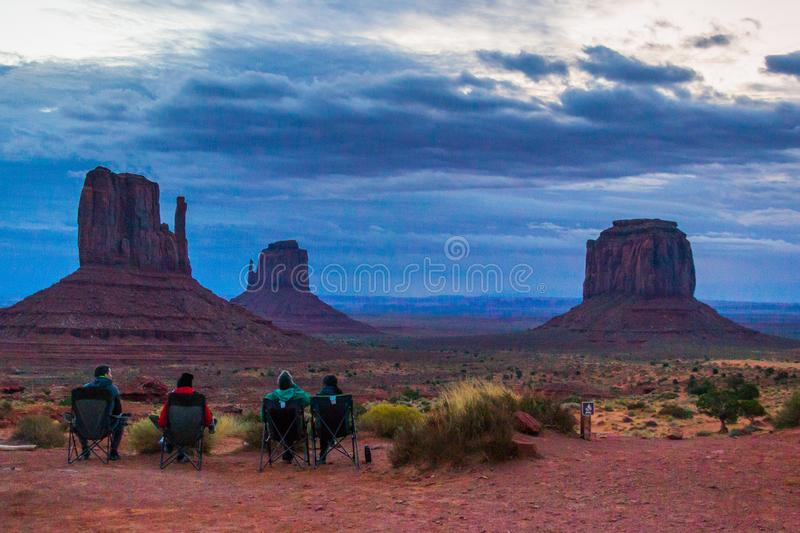 Monument valley mesas at dawn. Four seated people watching the picturesque show of mesas of the Monument valley at sunrise stock images