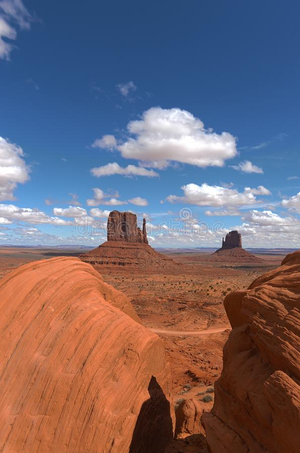 Monument Valley National Park vertical shot. Monument Valley vertical shot with blue sky and clouds with rocks on the foreground royalty free stock photography