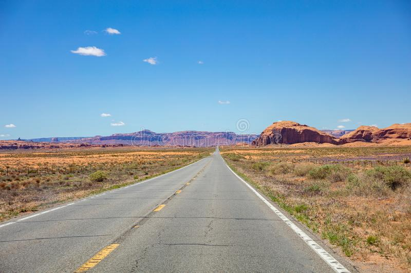 Monument Valley highway, Tribal Park in the Arizona-Utah border, USA. Monument Valley road, Navajo Tribal Park in the Arizona-Utah border, USA. Scenic highway to royalty free stock photos