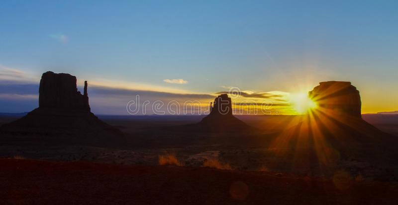 Monument Valley at sunrise with iconic West and East Mitten Buttes, Arizona USA. Monument Valley Navajo Tribal Park sprawls across the Arizona and Utah state stock image
