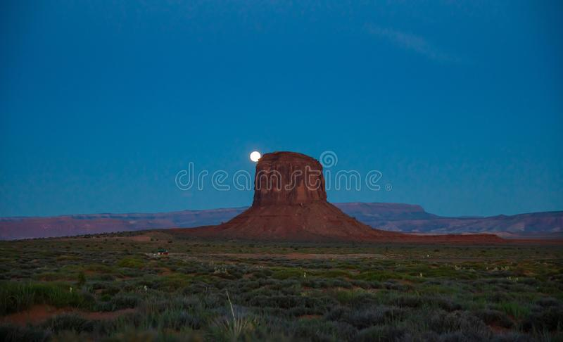 Monument Valley Tribal Park in the Arizona-Utah border, USA. Monument Valley, Fullmoon in spring. Red rocks against dark blue sky. Navajo Tribal Park in the stock photography