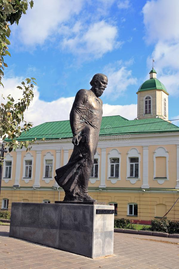 Monument zum russischen Verfasser Dostoevsky in Omsk gegen den Hintergrund des Gebäudes der Wachstube von der 18. lizenzfreies stockfoto