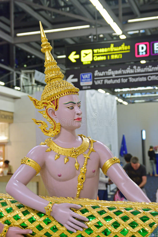 Monumental Sculpture of Demigods trying to pull a Dragon in Suvarnabhumi Airport. Monumental Sculpture of Demigods with elegant golden crown and accessories stock photos
