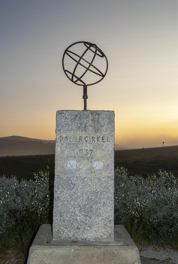 Monumentet f?r arktisk cirkel som t?nds av den midnatta solen royaltyfria bilder