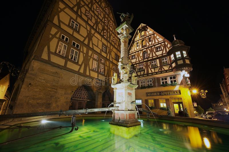 Monumenti storici con la fontana alla priorità alta alla notte in Rothenburg Ob'Der Tauber, Germania fotografia stock libera da diritti