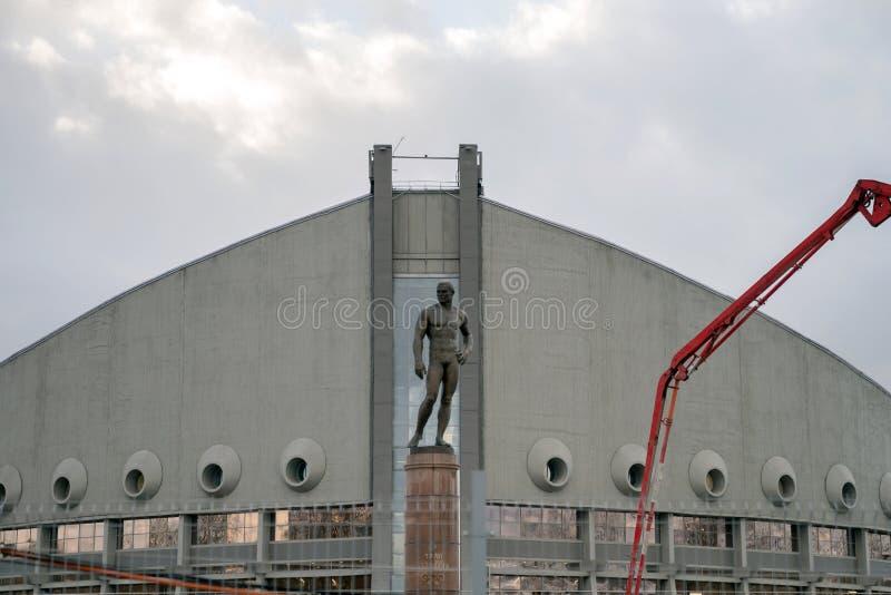 Monumento ad Ivan Yarygin, campione olimpico nel lottare di stile libero, contro lo sfondo del palazzo degli sport in Krasnojarsk fotografia stock libera da diritti