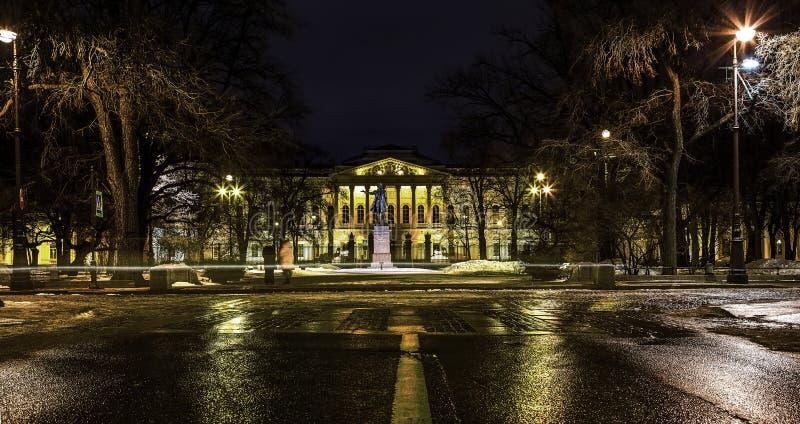 Monumento a Alexander Pushkin en el parque de Mikhailovsky en el teatro de Mikhailovsky, la reflexión de luces en el mojado imagen de archivo