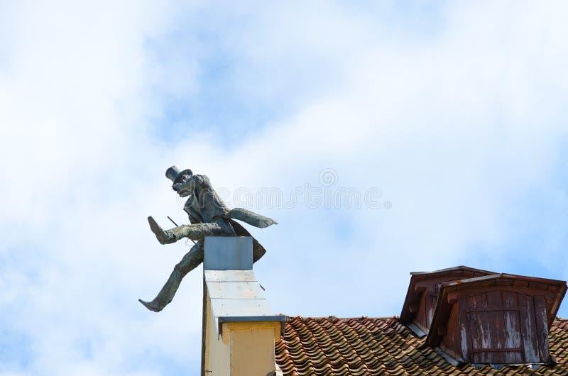 Monumento ao chimneysweep no telhado, Klaipeda, Lituânia fotos de stock royalty free