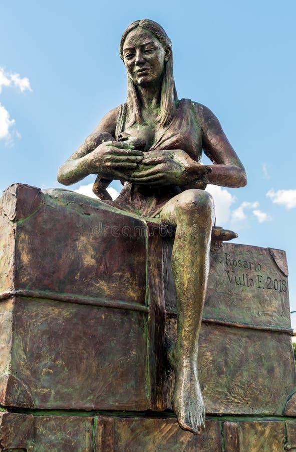 Monumento de bronce al emigrante, mujer que cuida al ni?o, por Rosario Vullo, situado en el parque del delle Femmine de Isola fotos de archivo libres de regalías