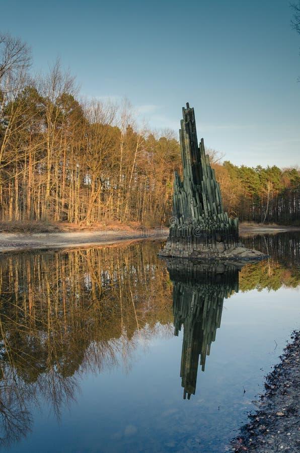 Monumento del basalto nello stagno vicino a Rakotzbrucke, Germania fotografia stock