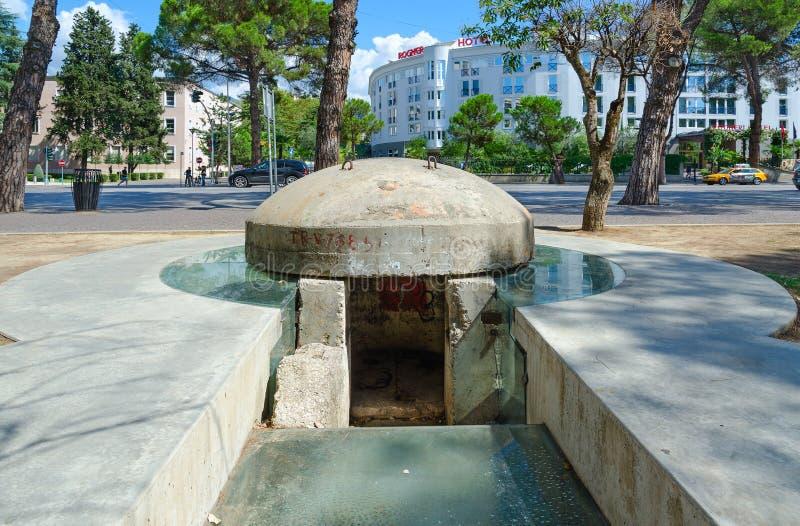 Monumento-depósito TR-V-76851, no fundo - hotel Rogner, Tirana, Albânia fotografia de stock royalty free