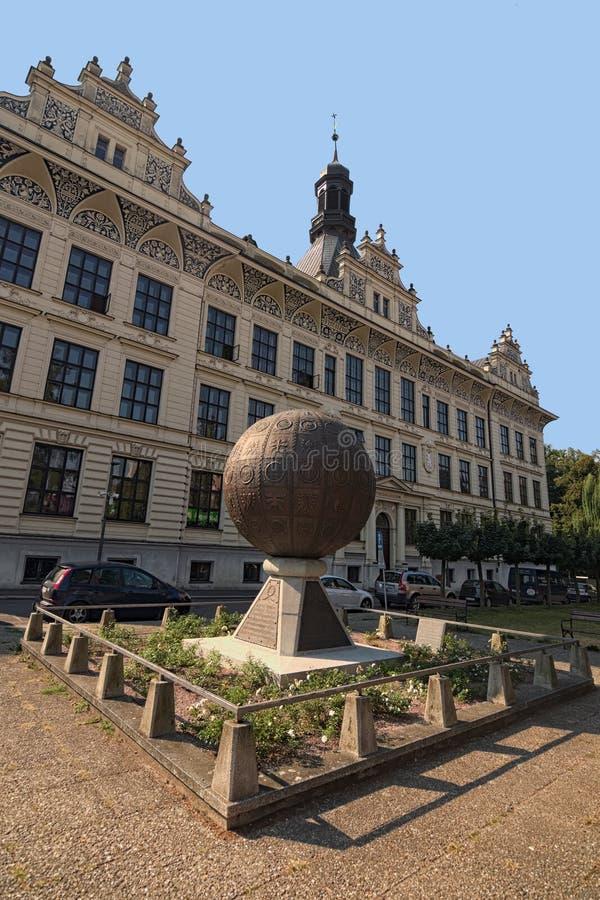 Monumento inusual bajo la forma de bola de metal con las imágenes grabadas en relieve Edificio antiguo hermoso en el fondo fotos de archivo
