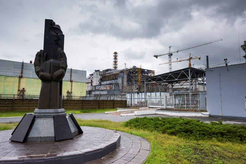 Monumento a los administradores judiciales de Chernóbil con el cuarto reactor en el fondo foto de archivo libre de regalías