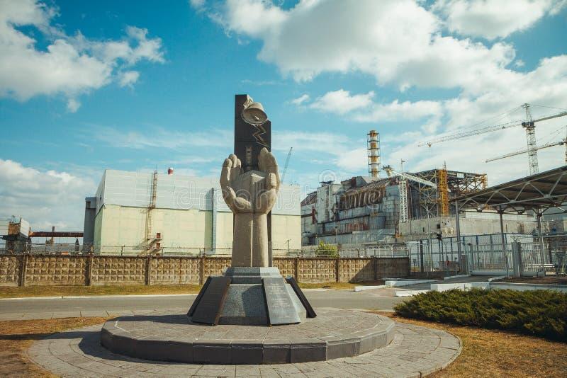 Monumento a los administradores judiciales de Chernóbil y al cuarto reactor sin el cerco del sarcófago Central nuclear de Chornob fotografía de archivo libre de regalías