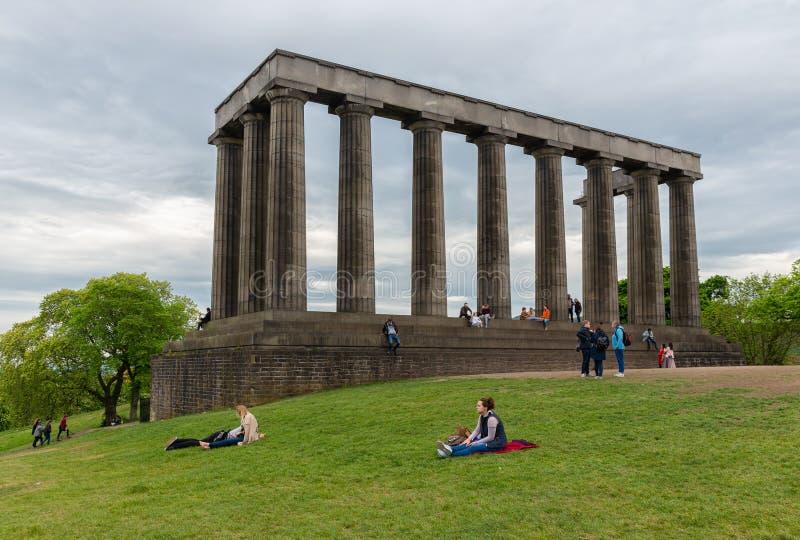 Monumento nacional Escocia en la colina Edimburgo de Calton con la reconstrucción de gente imágenes de archivo libres de regalías