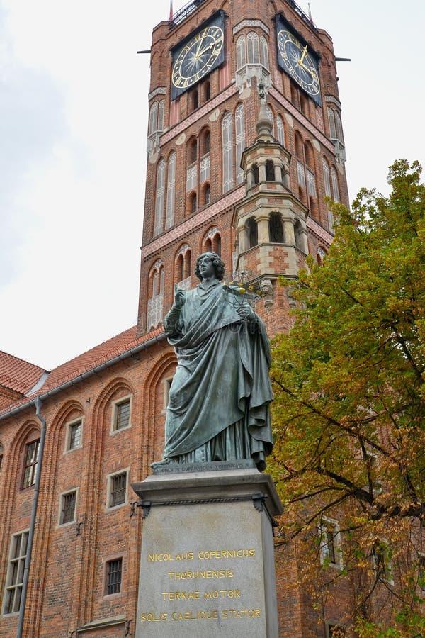 Monumento a Nikolai Copernicus 1853 contra o fundo da torre de relógio da antiga prefeitura Torun, Polônia fotos de stock
