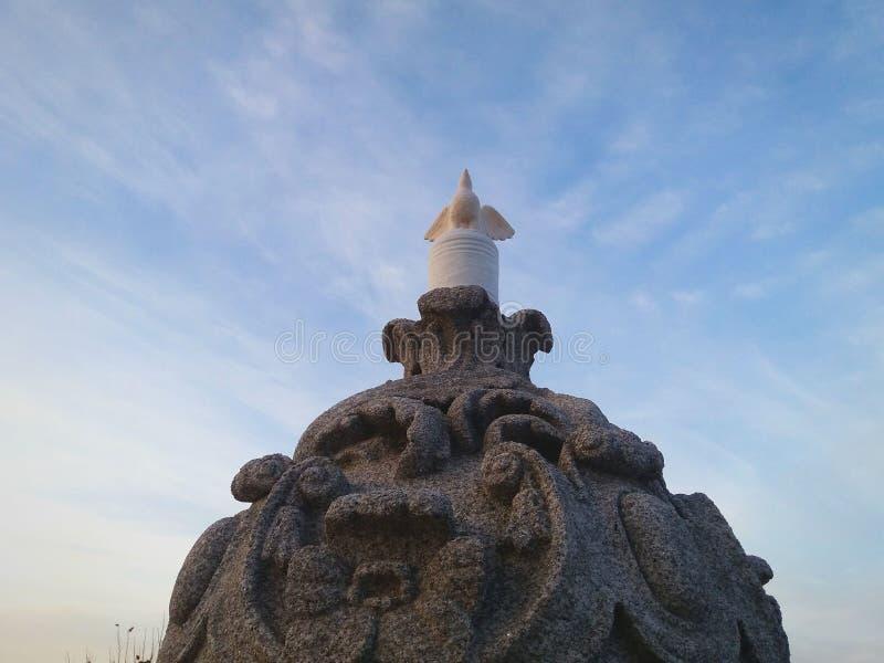 Monumento spettacolare con una colomba sopra e con un fondo una b immagine stock libera da diritti